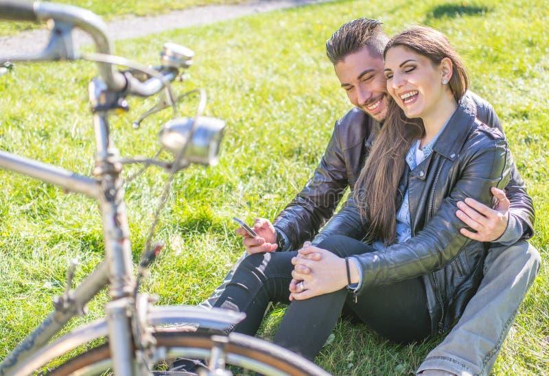 Paarzitting op het gras en het ontspannen stock foto