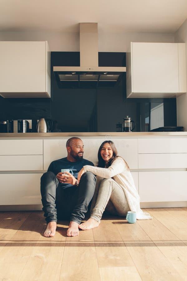 Paarzitting op keukenvloer en het hebben van koffie royalty-vrije stock foto