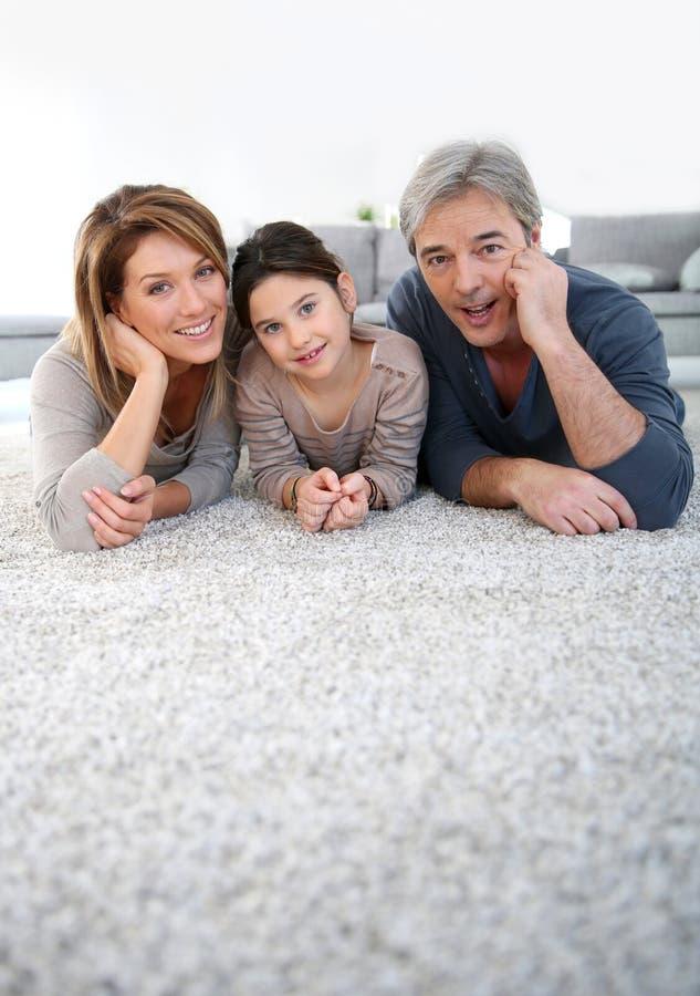 Paarzitting op middelbare leeftijd op tapijtvloer stock foto's