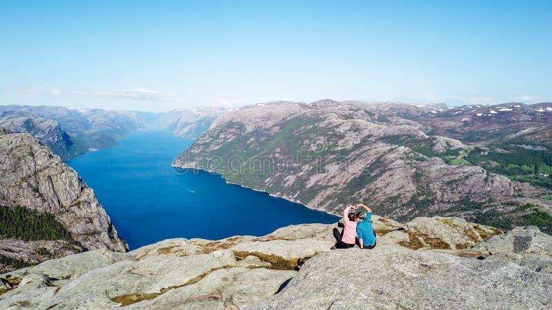 Paarzitting op rots die van de fjordmening geniet, dichtbij Preikestolen, Noorwegen Zij vormen een hart met hun handen stock foto