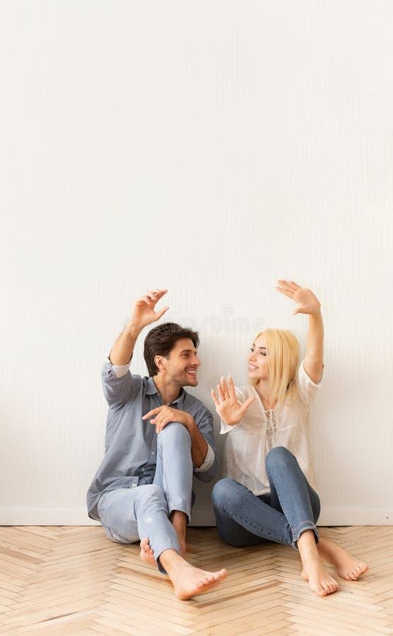 Paarzitting op Vloer die Binnenlandse Ontwerpideeën voor Huis delen stock foto