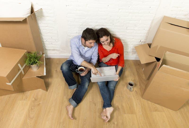 paarzitting op vloer die zich in nieuw huis bewegen die meubilair met computerlaptop kiezen stock fotografie