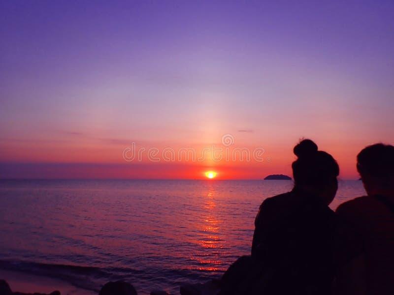 Paarzitting samen met mooie en echt kleurrijke zonsondergang met kleurrijke hierboven hemel royalty-vrije stock foto