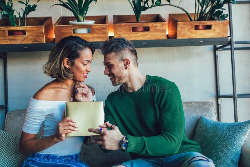 Paarzitting tussen verschillende rassen in koffiebar Mens die gift geven aan zijn meisje royalty-vrije stock fotografie