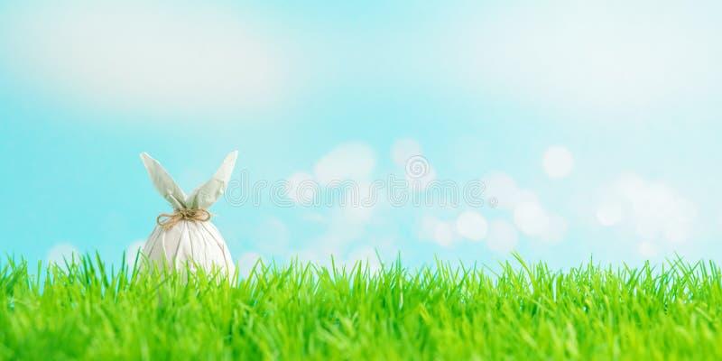 Paasei dat in een document in de vorm van een konijntje op groen gras wordt verpakt Het concept van de de lentevakantie royalty-vrije stock foto