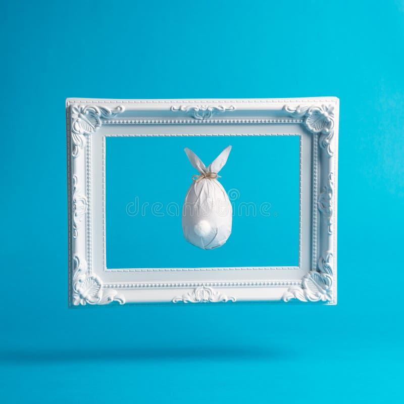 Paasei in een document in de vorm van een konijntje met wit uitstekend kader wordt verpakt dat Minimaal Pasen-concept royalty-vrije stock afbeeldingen