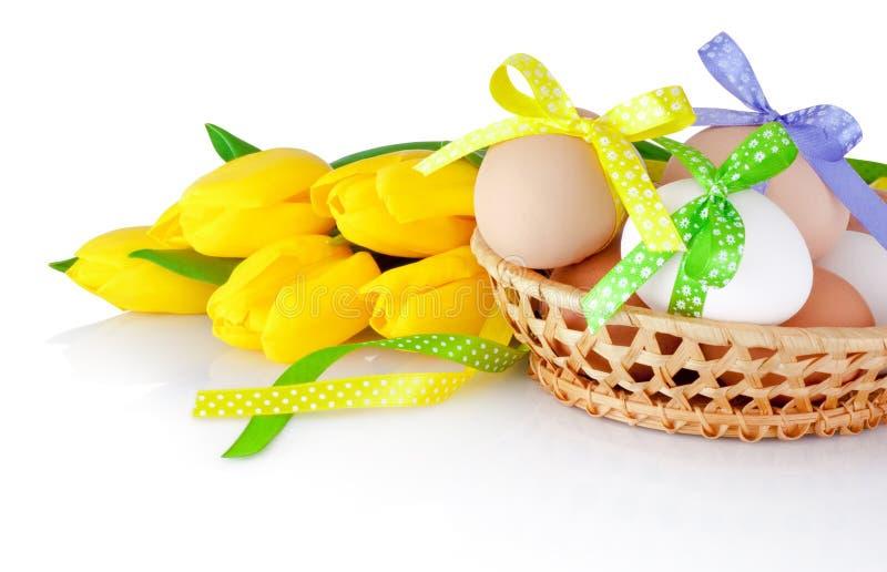 Paaseieren in de mand en de gele tulpen die op een wit wordt geïsoleerd royalty-vrije stock fotografie