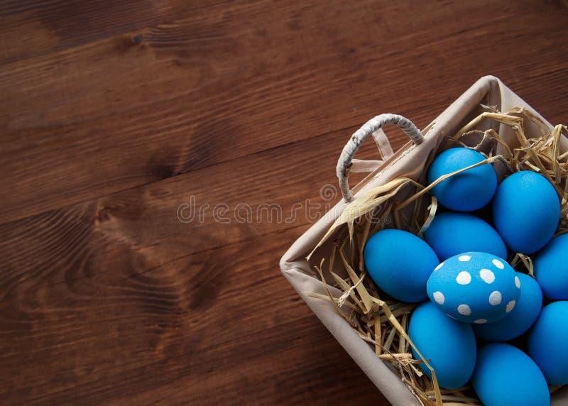 Paaseieren in een mand op rustieke houten achtergrond, selectief nadrukbeeld, Gelukkige Pasen stock fotografie