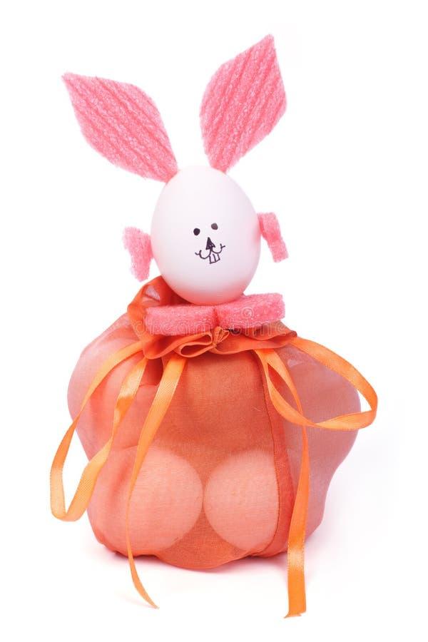 Paaseieren in een zak en een konijntje met roze oren stock foto's