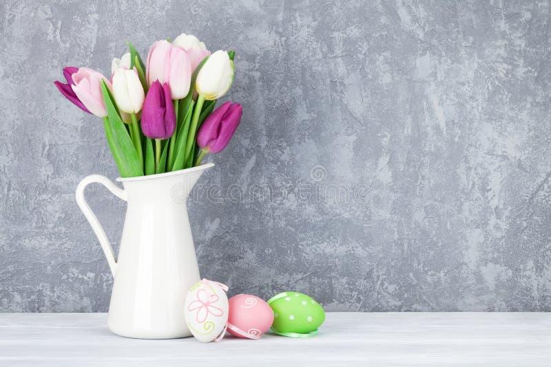 Paaseieren en kleurrijke tulpen stock afbeelding