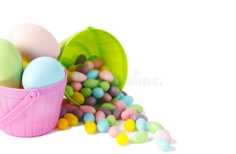 Paaseieren en suikergoed in kleurrijke manden op witte achtergrond, exemplaarruimte stock afbeelding