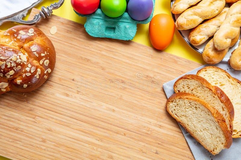 Paaseieren en tsourekivlecht, het Griekse zoete brood van Pasen, op hout stock afbeeldingen