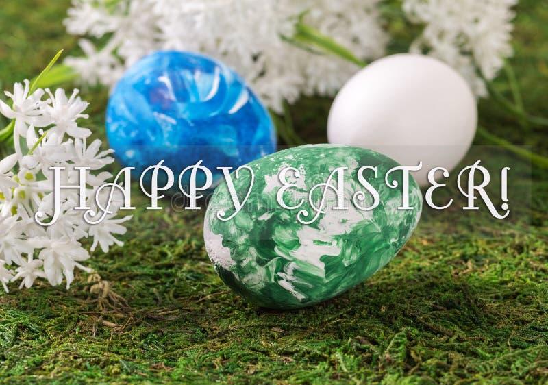 Paaseieren en witte bloemen op een achtergrond van gras met een felicitatietex stock foto