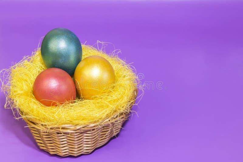 Paaseieren in gouden gele roze groene kleur in een nest in een rieten mand op een lilac achtergrond worden geverft die stock foto's