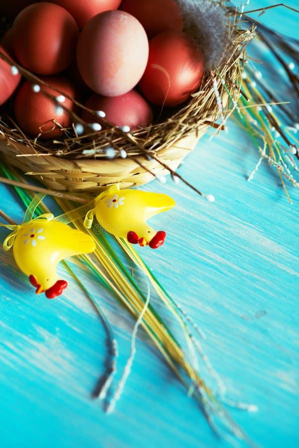 Paaseieren in het nest, die op blauwe houten achtergrond voorbereidingen treffen stock foto's