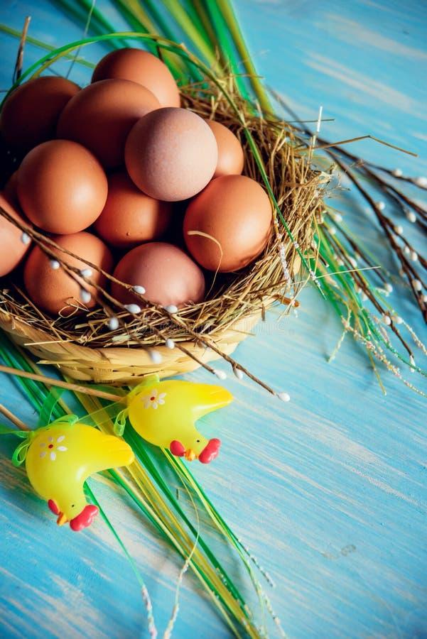 Paaseieren in het nest, die op blauwe houten achtergrond voorbereidingen treffen stock afbeelding