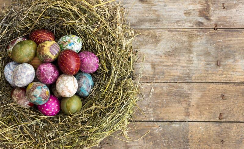 Paaseieren in het nest op rustieke houten achtergrond stock foto