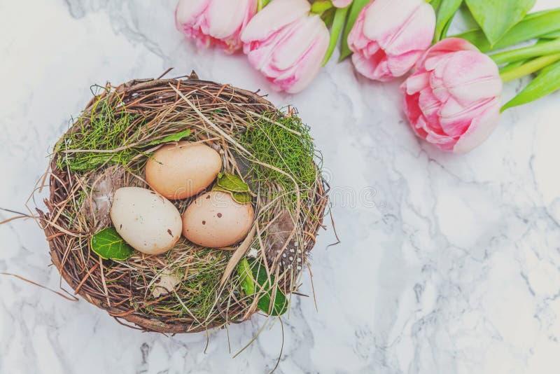 Paaseieren in nest met mos en roze vers tulpenboeket op marmeren achtergrond royalty-vrije stock afbeelding
