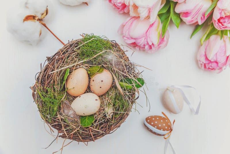 Paaseieren in nest met moskatoen en roze vers tulpenboeket op rustieke witte houten paaseieren als achtergrond in nest met mos stock foto
