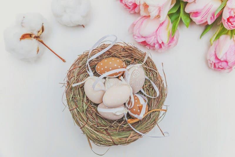Paaseieren in nest met moskatoen en roze vers tulpenboeket op rustieke witte houten paaseieren als achtergrond in nest met mos stock afbeeldingen