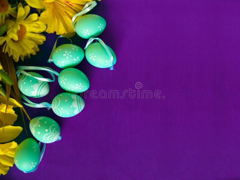 Paaseieren op purpere zijde, met gele bloemen royalty-vrije stock afbeeldingen
