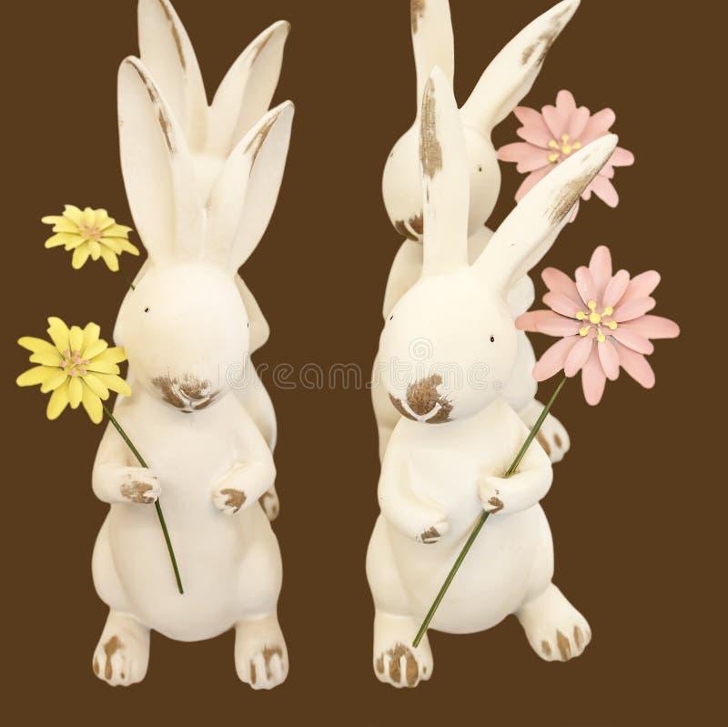 Paashaasdans vier kleine konijnen die bloemen houden zijn in vorming doend een Pasen-geïsoleerde dans - royalty-vrije stock foto