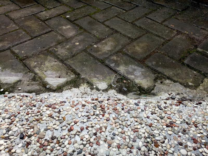 Pabble and paving stone. PMR B-5 home terrace floor combination of rocky gravel and paving stock images