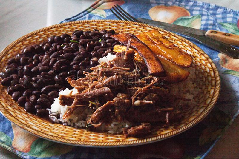 Pabellón Criollo traditional venezuelan dish. Traditional Venezuelan dish Pabellon Criollo. White rice,Shredded Beef, Black beans, Fried Plantains. Lunch time royalty free stock photography