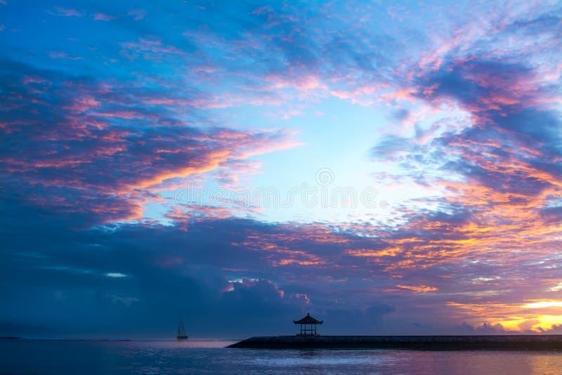 Pabellón y barco de navegación en el océano durante puesta del sol imagen de archivo