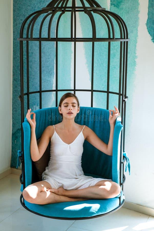 pacífico y tranquilo La mujer se relaja en la posición de loto en casa La mujer bonita aprende meditar Concentrado lindo de la mu fotos de archivo