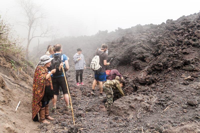PACAYA, GUATEMALA - 28 MARZO 2016: Turisti che arrostiscono caramella gommosa e molle al giacimento di lava del vulcano di Pacaya immagine stock