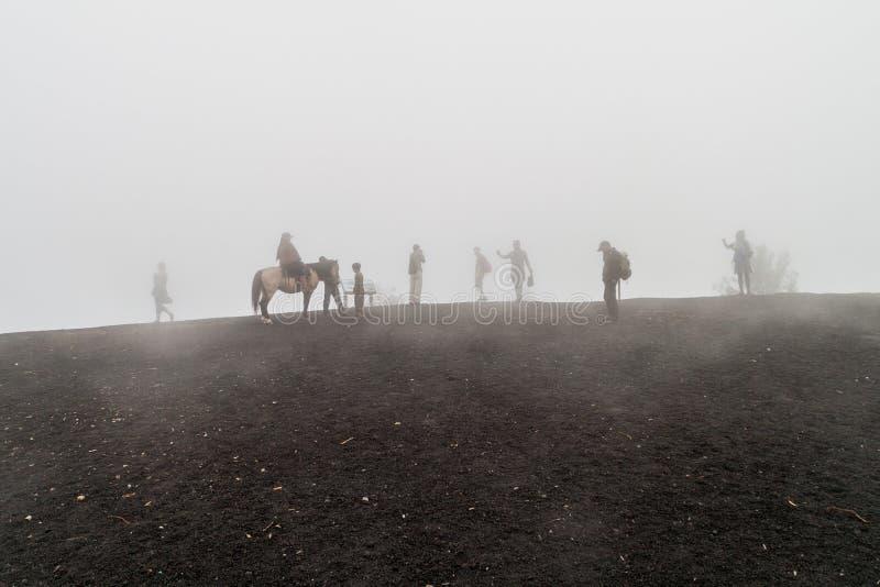 PACAYA, GUATEMALA - 28 MARZO 2016: Turisti che visitano il vulcano di Pacaya nella foschia, Guatema immagini stock libere da diritti