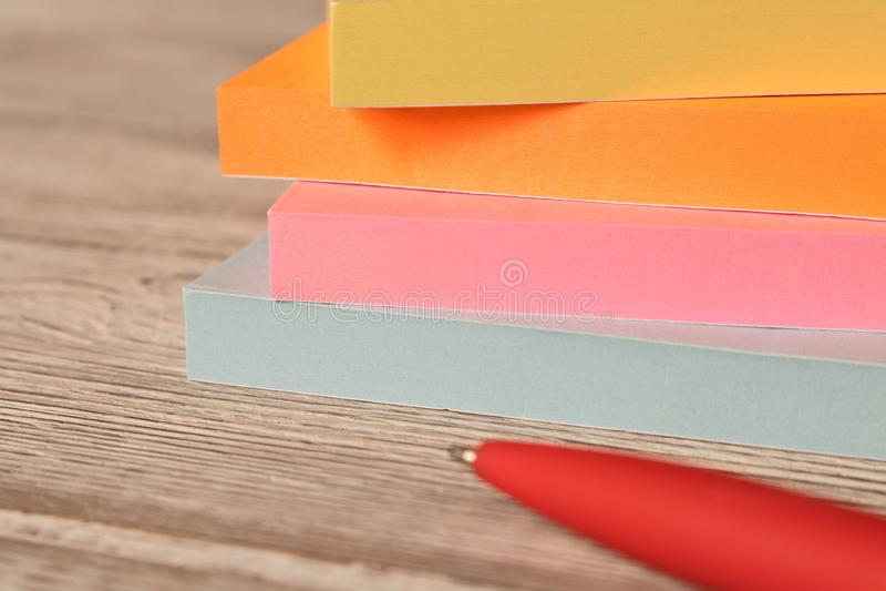 Pacchetti degli autoadesivi variopinti per le note e una penna su una tavola di legno fotografia stock