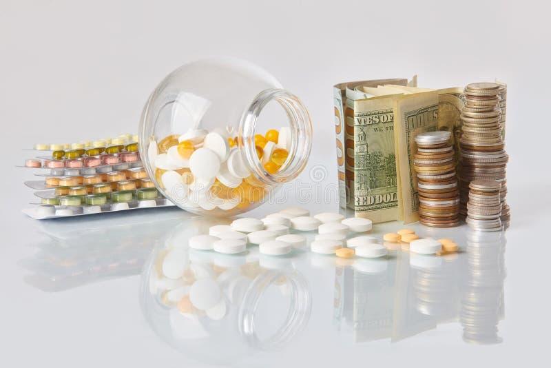 Pacchetto delle pillole della medicina con tre pacchetti delle monete e della bottiglia di vetro con il denaro contante del dolla fotografie stock libere da diritti