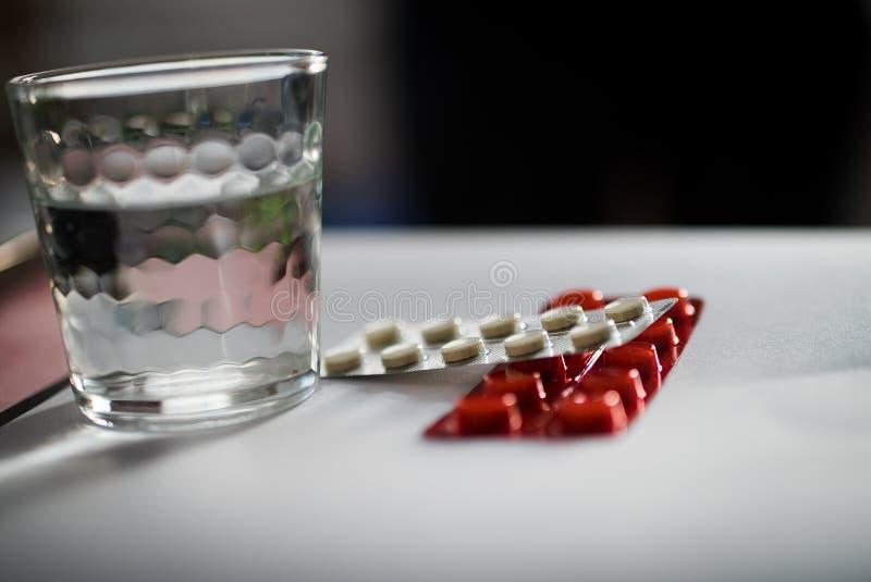 Pacchetto delle pillole e del bicchiere d'acqua immagini stock libere da diritti