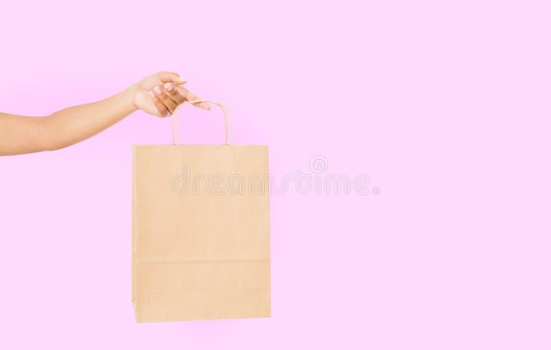 Pacchetto dello spazio in bianco del modello Mano afroamericana della donna che tiene una borsa di carta di Kraft su fondo rosa C immagine stock libera da diritti