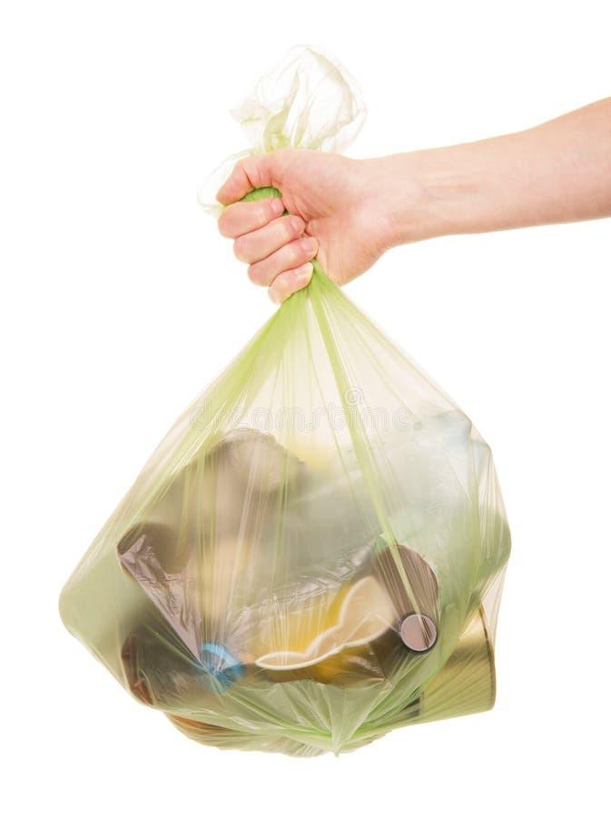 Pacchetto femminile della tenuta della mano con i rifiuti domestici isolati su bianco immagini stock