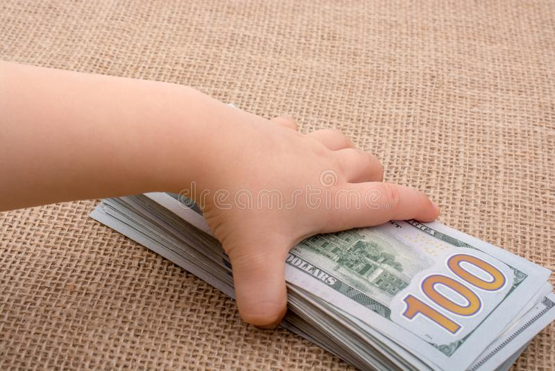 Pacco della banconota della tenuta della mano del bambino del dollaro americano a disposizione fotografie stock