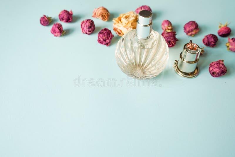 Pachnidło butelka z wzrastał kwiaty na błękitnym tle Kwiecisty perfumowania poj?cie Odg?rny widok kosmos kopii obraz stock