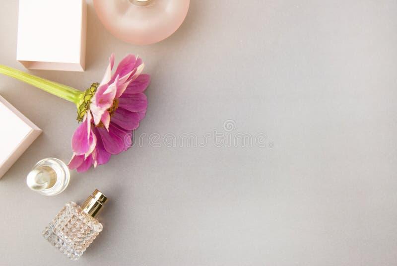 Pachnidło butelki z menchiami kwitną na lekkim tle Mydlarnia, kosmetyki, woni kolekcja Mieszkanie nieatutowy kosmos kopii fotografia stock