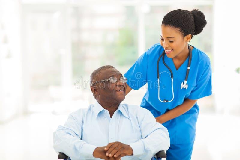 Paciente africano del mayor de la enfermera imagen de archivo libre de regalías