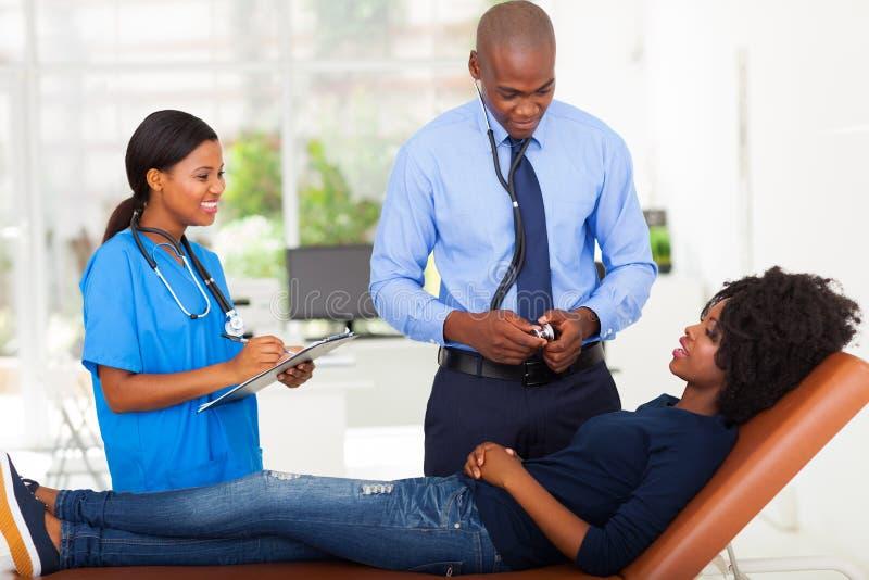 Doctor paciente que examina foto de archivo libre de regalías
