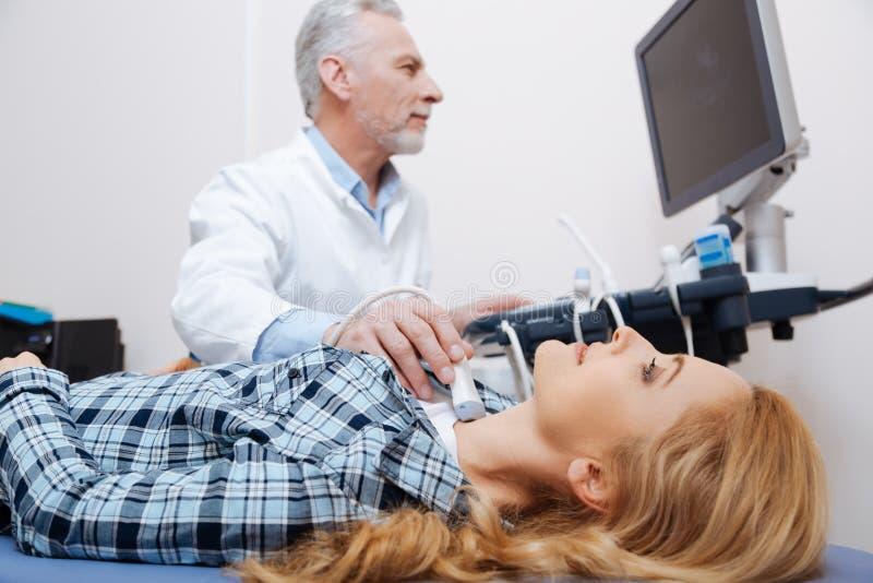 Paciente alegre tendo o controle do ultrassom do tiroide na clínica fotografia de stock