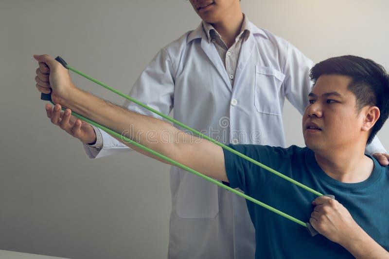 Paciente ascendente próximo da mão que faz esticando o exercício com uma faixa flexível do exercício e uma mão do fisioterapeuta  fotos de stock royalty free