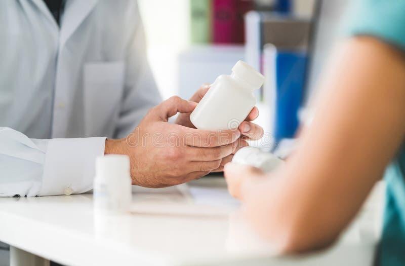 Paciente asesor del doctor sobre la medicación derecha Médico que sostiene la medicina y píldoras a disposición imagenes de archivo