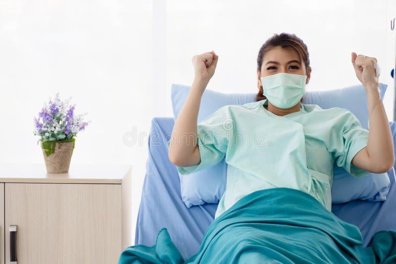 Paciente asiático das mulheres que senta-se na cama e nos aumentos de hospital seus braços A jovem mulher para recuperar da doen? foto de stock royalty free