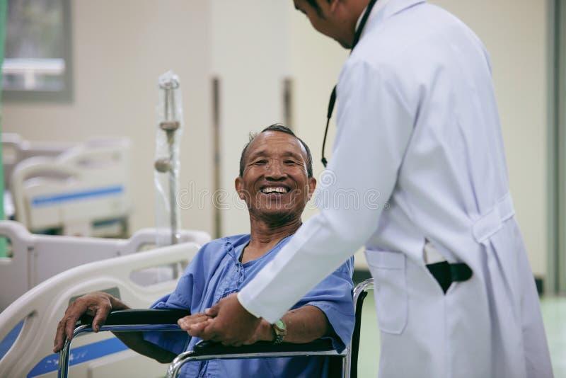 Paciente asiático na cadeira de rodas que senta-se no hospital com docto asiático foto de stock