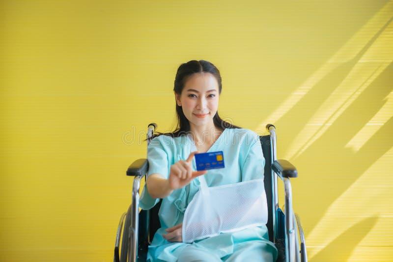 Paciente bonito asiático das mulheres que aparece o cartão de saúde e que senta-se na cadeira de rodas no hospital, feliz e sorri imagem de stock royalty free