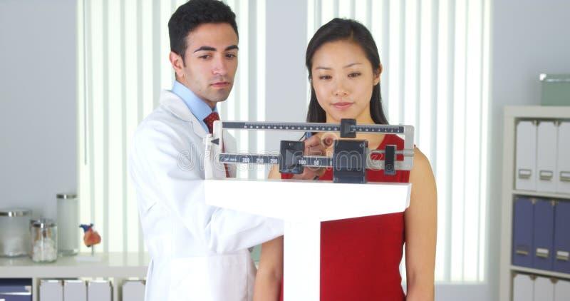 Paciente chino feliz que es pesado en escalas fotografía de archivo