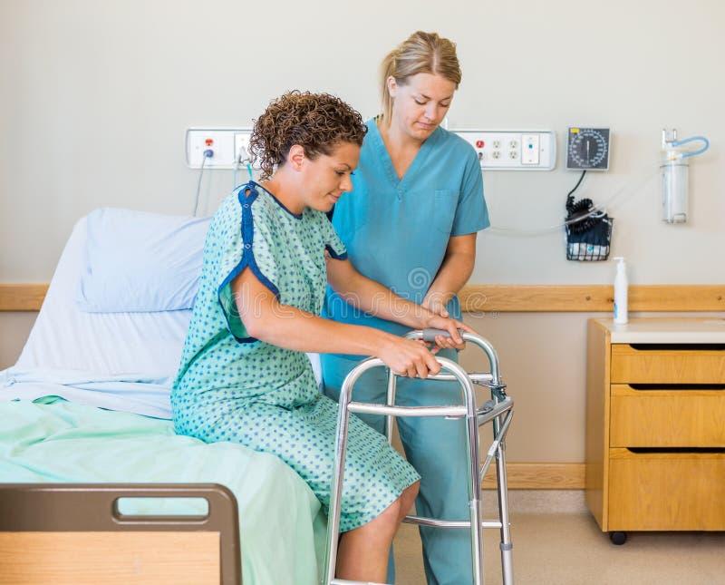 Paciente com Walker While Nurse Assisting Her dentro foto de stock